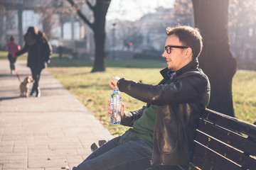 Man sitting on park bench and opening bottle of water