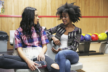 Friends talking to each other at bowling center