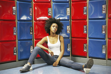 Beautiful young woman sitting in front of lockers