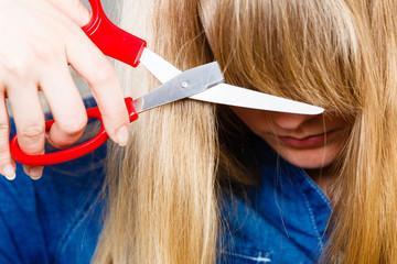 Woman cutting her fringe.
