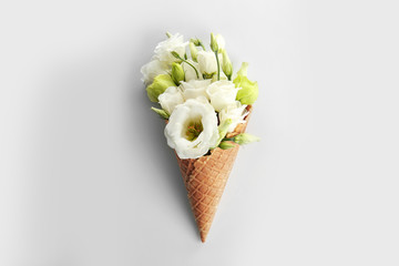 Waffle cone with bouquet of beautiful flowers on white background