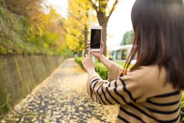 Woman taking photo by cellphone at autumn season