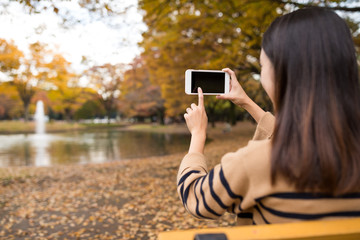 Woman taking photo at park in autumn season