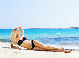 Woman posing in a black swimsuit on the beach