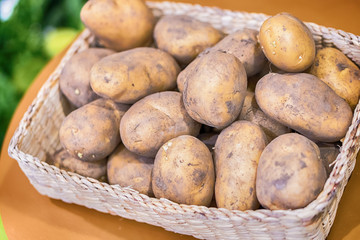 top view of new potatoes in a basket on a gray wooden background