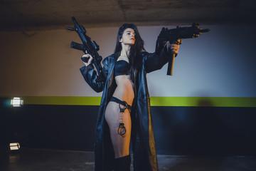 Army brunette girl with gun in a garage in attitude shoot, dress