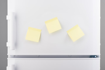 Three blank yellow sticky paper notes on white refrigerator