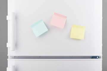Yellow, pink and blue sticky paper notes on white refrigerator