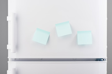 Three blank light blue sticky paper notes on white refrigerator