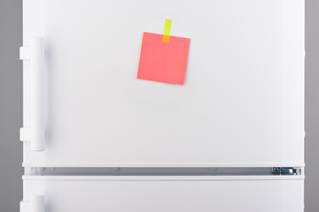 Pink note attached with yellow sticker on white refrigerator