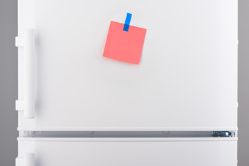 Pink paper note attached with blue sticker on white refrigerator