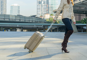 travel background, woman tourist walking with suitcase  at trans
