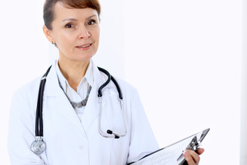 Happy female doctor standing in hospital and filling up medical form. Medicine and health care concept.