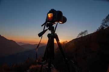camera mounted on a tripod to photograph the sunset