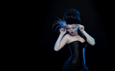 actress brunette woman with high hair, a mask with feathers and corset in old style on a black background