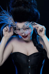 brunette woman with high hair, wearing a mask with feathers and corset in old style on a black background