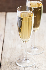 Champagne in glasses on old wooden table, selective focus