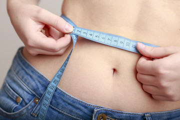fair-skinned woman in blue jeans is measured using a tape beautiful slender waist