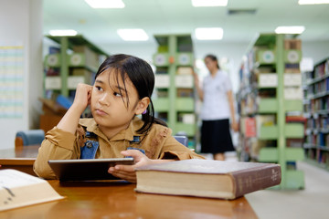 Education school concept. Asian female student study in school library, using tablet and searching on internet