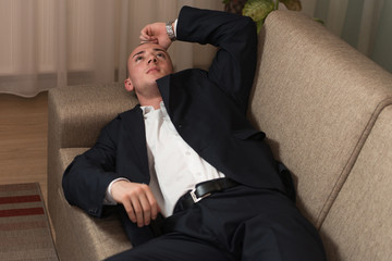 Young Businessman Sleeping on Sofa at Home