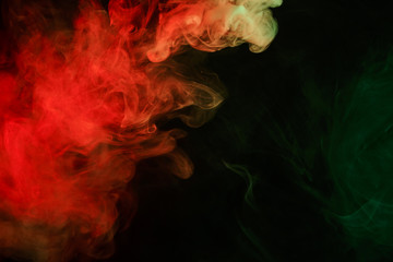 Abstract smoke Weipa. Personal vaporizers fragrant steam. The concept of alternative non-nicotine smoking. Red green smoke on a black background. E-cigarette. Evaporator. Taking Close-up. Vaping.