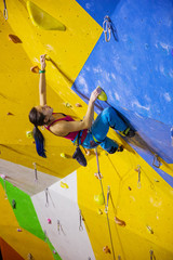 Female rock climber in climbing gym