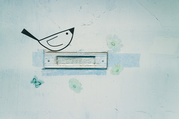 Closeup image of a letterbox slot in a light-blue door. Around the slot a cute bird, a butterfly and some flowers. The slot is sealed with tapes.