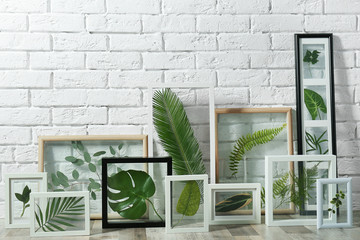 White frames with green leaves on brick wall background