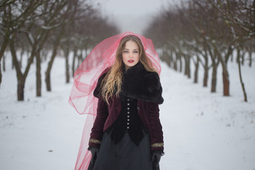 girl in a red veil on the snow in the winter