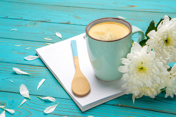 cup of coffee and flowers on light wooden table