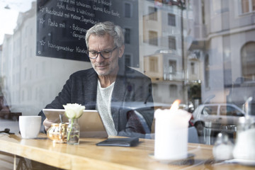 Mature man with tablet in a cafe