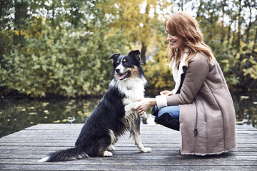 Smiling woman with her dog on jetty in autumn
