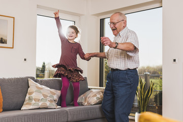 Gra´ndfather and granddaughter jumping and dancing on couch
