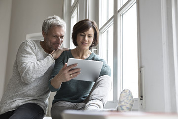 Couple sharing tablet at the window