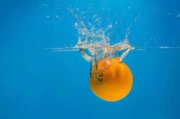 Orange splashing in water with blue background