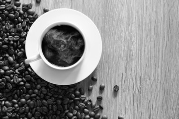 White coffee cup and pile of coffee seeds on brown wooden plate / Top view and Select focus image, Space for text, black and white