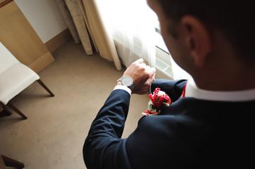 Wedding groom detail - the groom puts on the clock
