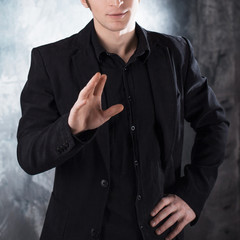 Say no. Young man conducts a dialogue in black suit on textured grey background