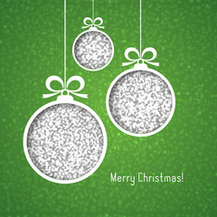 White Christmas balls, made of silver glitter, cut paper on green background.