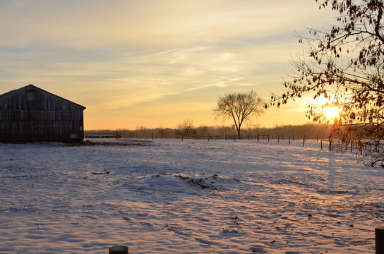 Sunrise casting a golden glow on the farm on a snowy winter morning