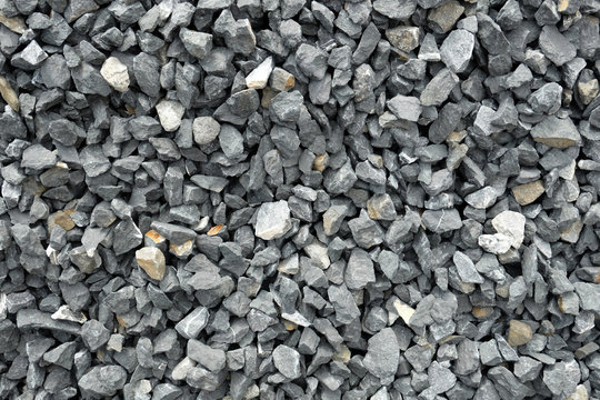 stone aggregate - a stack of gray gravel, coarse loose stones with very irregular shapes, crushed and broken at a stonepit into similar sizes. Some of the stones are light grey or even yellow.