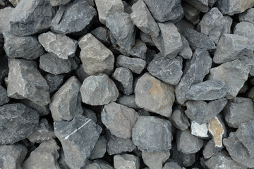 loose large stones - gray gavel aggregate of different sized stone pieces crushed and broken into irregular shapes and sizes at a stonepit.