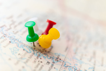 Travel destination points on a map indicated with colorful thumbtacks and shallow depth of field