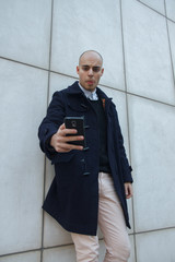 Young handsome bald businessman holding a smart phone, looking down tapping screen leaning against a white wall - technology, business, work concept