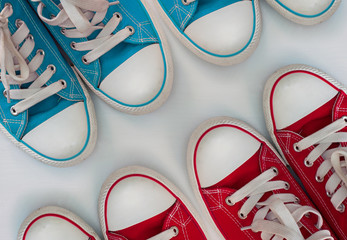 Four pairs  sneakers on a white wooden surface
