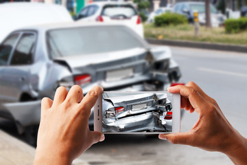 Close up hand holding smartphone take photo of car accident