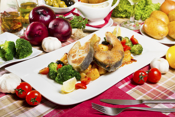 Two fried carp steaks served on a white plate with boiled potatoes and broccoli next to fresh vegetables.