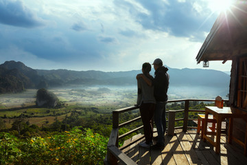 Silhouette couple looking at the beautiful sunrise on the top of mountain with the view into misty