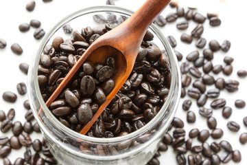 roasted coffee beans in wooden spoon and glass jar on white