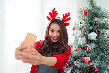 Woman take selfie on phone with Christmas hat hold christmas gif